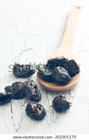 pitted prunes on old table - stock photo
