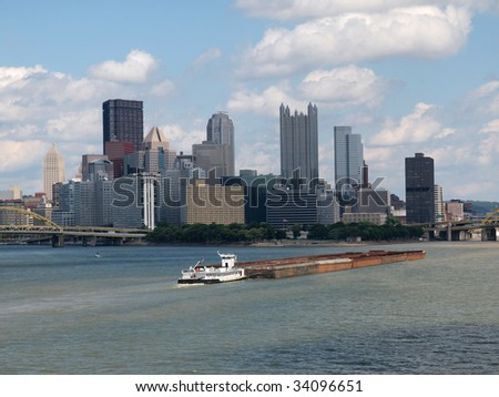 Pittsburgh riverfront with large barge in motion. - stock photo