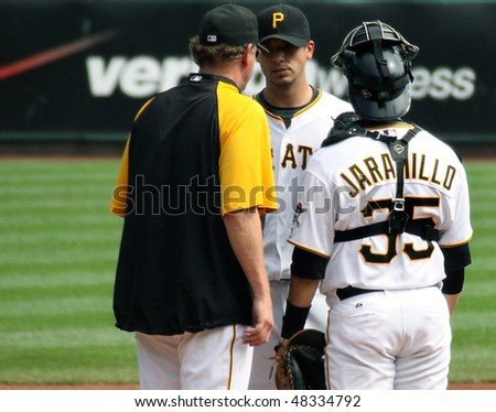 PITTSBURGH - SEPTEMBER 24: Pittsburgh Pirates' pitching coach, Joe Kerrigan speaks with Charlie Morton during a game against Cincinnati Reds on September 24, 2009 in Pittsburgh, PA. - stock photo