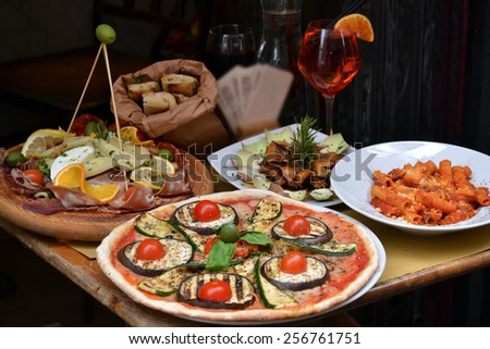 Pizza and food arrangement outside an italian restaurant. - stock photo