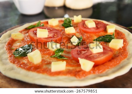 pizza and ingredients for pizza on the wooden background - stock photo