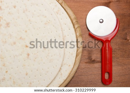 Pizza base - cake next round knife for cutting pizza. - stock photo
