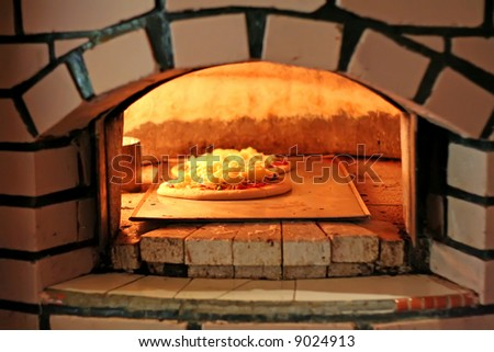 Pizza being baked in a wood fire brick oven in a restaurant - stock photo