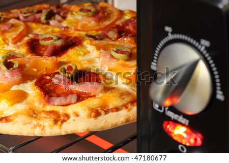 pizza being cooked  in oven-shallow DOF - stock photo