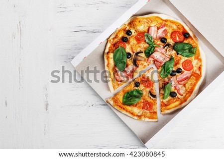PIZZA BOX delivery concept. Open box with hot tasty italian SLICED pizza with bacon, olives, basil, tomato, nushrooms. Much space for text - stock photo