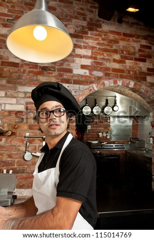 Pizza Chef is standing at the kitchen in a pizza restaurant working making dough while listening to customers orders - stock photo