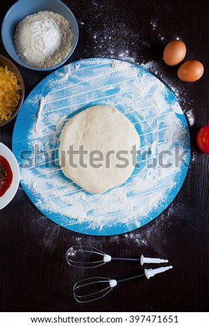 Pizza cooking ingredients. Raw pizza ingredients - dough, sauce, cheese, tomato, flour, eggs. - stock photo