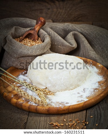 Pizza dough on old wooden table - stock photo
