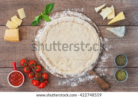 Pizza dough with ingredients on a old wooden board on background. Top view.  - stock photo