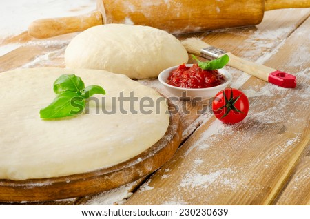 pizza dough with tomato sauce and basil on  wooden table - stock photo