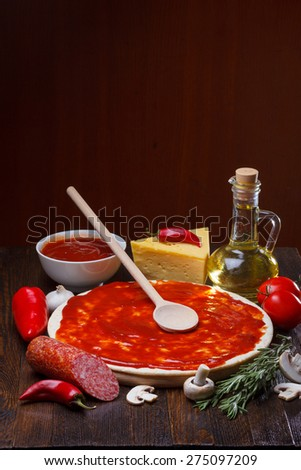 Pizza dough with tomato sauce during preparation, with a lot of ingredients on wooden table