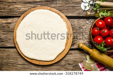 Pizza dough with tomatoes, and herbs with a rolling pin. On wooden background. Top view - stock photo