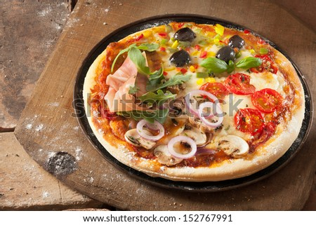 Pizza four seasons divided into quadrants with sliced prosciutto ham, vegetarian with onion and mushroom, cheese and tomato and olives and cheese - stock photo