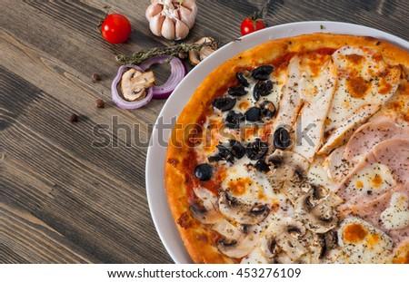 "Pizza ""Four Seasons"" with ham, mushroom, meat, olive on wood table - stock photo"