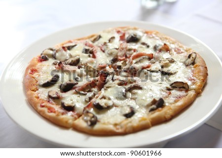 Pizza ham ans mushroom slice lifted with cheese strings - stock photo