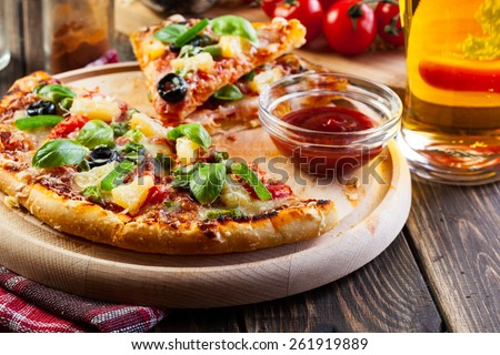 Pizza hawaii with beer served on cutting board - stock photo