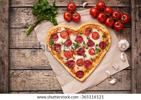 Pizza heart shaped with pepperoni, tomatoes, mozzarella, garlic and parsley on vintage wooden table background. Concept of romantic love for Valentines Day. - stock photo