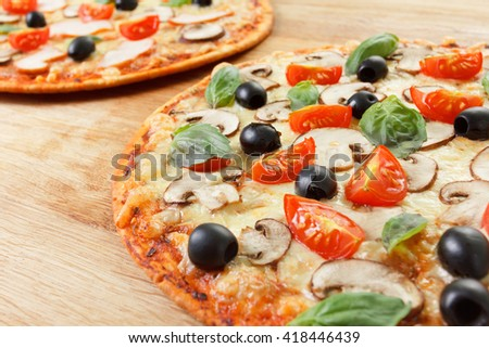 Pizza homemade  with mushrooms, olives and tomatoes. Basil, rosemary and fresh vegetables