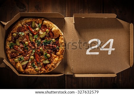 pizza in the in delivery box with 24 time text on the wood - stock photo