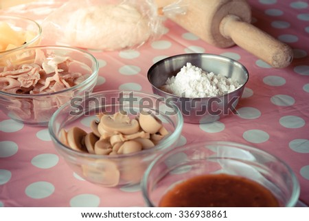 Pizza ingredient with mushroom ham pineapple dough and sauce on pink table , process in vintage style - stock photo