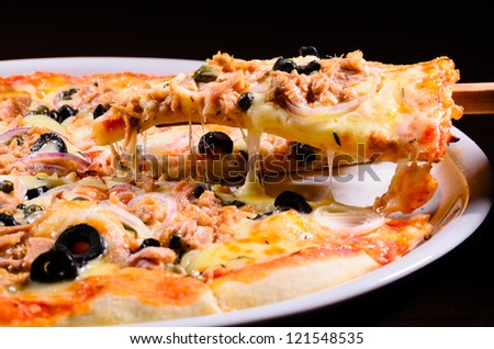 Pizza lifted slice with tuna isolated over black  background