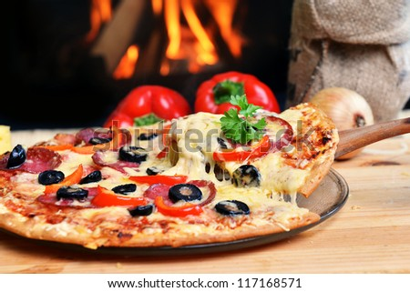 Pizza lifting slice with pepperoni and olives - stock photo
