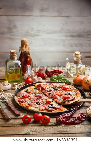 Pizza made with salami, mozzarella, mushrooms, olives and tomato sauce  - stock photo