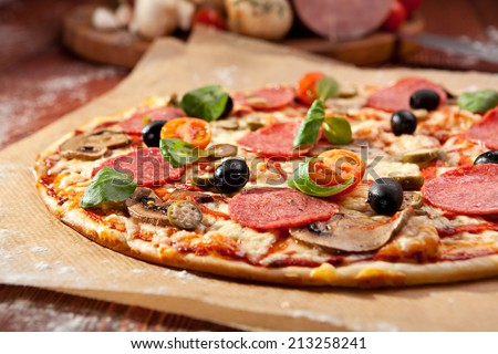 Pizza made with Salami, Mozzarella, Mushrooms, Olives and Tomato Sauce