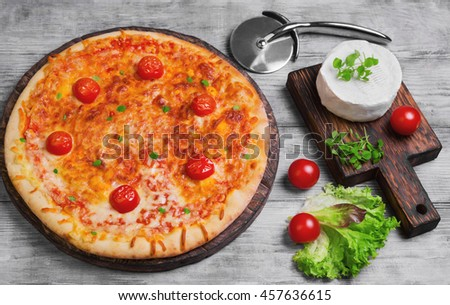 Pizza Margarita with cheese, cherry tomatoes, feta cheese, fresh herbs, round knife for pizza, light wooden background