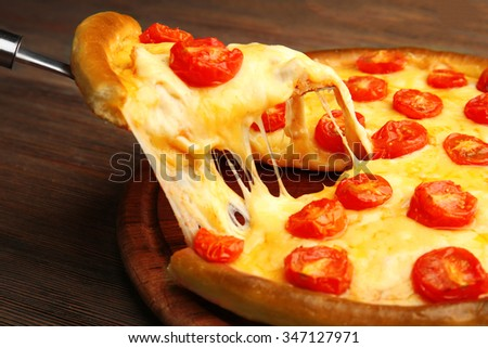 Pizza Margherita and removed slice on table - stock photo