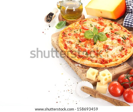 Pizza Margherita close to the ingredients like tomatoes, olive oil, cheese, basil, pepper and kitchen tools - stock photo