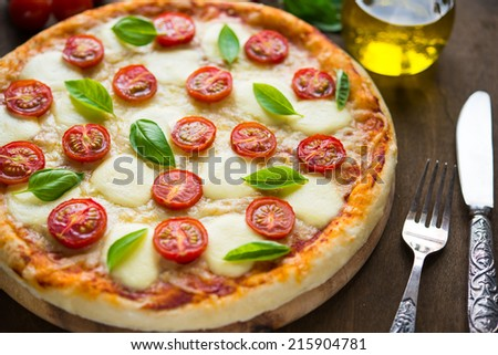 Pizza Margherita on dark wooden background - stock photo