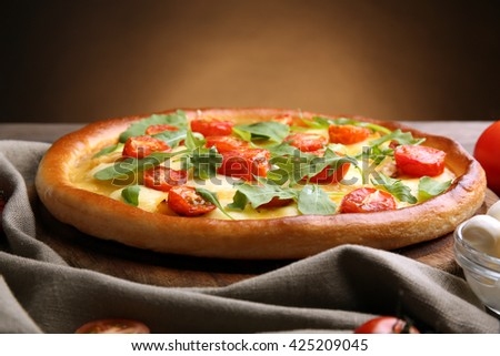 Pizza Margherita with arugula on brown background - stock photo