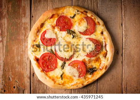 Pizza Margherita with tomatoes and mozzarella cheese on a wooden surface (horizontally oriented photo) - stock photo