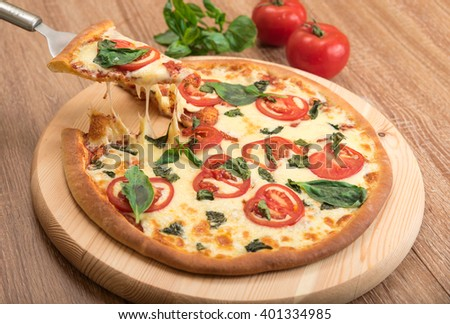 Pizza Margherita with tomatoes, mozzarella and basil on a wooden background, a slice of pizza with cheese stretching, close-up - stock photo