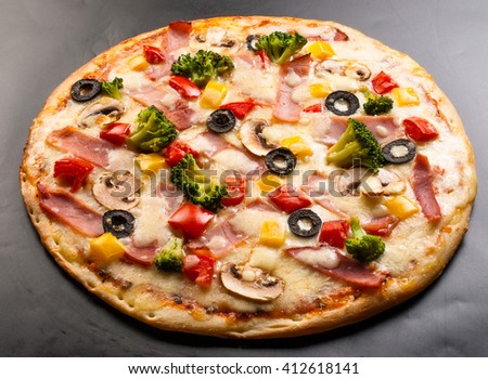 Pizza on a dark background with ham, mushrooms, cauliflower, olives, cheese and sweet pepper - stock photo
