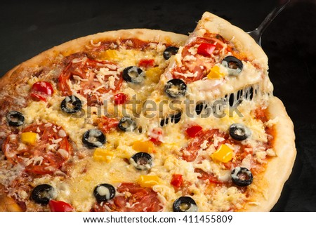 Pizza on a dark background with ham, mushrooms, olives, cheese and sweet pepper, cutting - stock photo