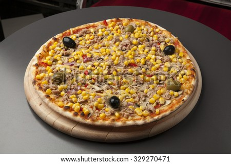 Pizza on a wooden plate with tuna and corn, black olives