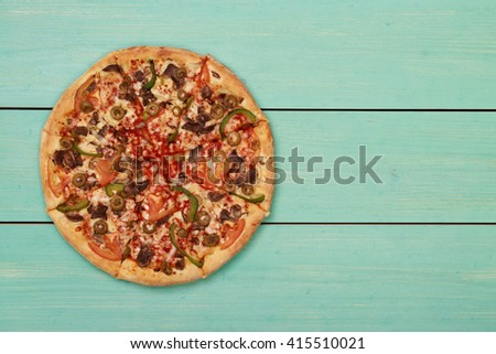 Pizza on mint wooden. Wooden table top view. On the table are the food for cooking. Healthy food. Dietetic foods. Above view on food. Hot Homemade Pepperoni Pizza Ready to Eat - stock photo