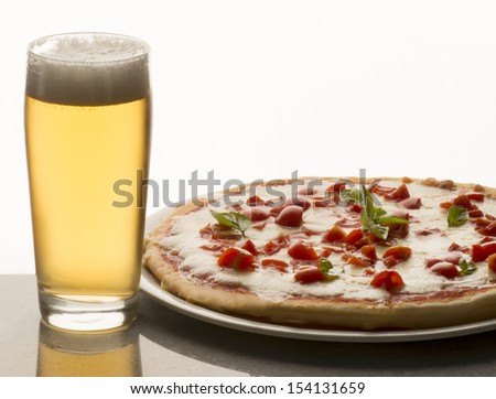 pizza on the table with  a glass of beer - stock photo