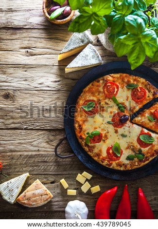 Pizza on wood with ingredients. Pizza with cheese, tomatoes and basil. Rustic italian pizza - stock photo