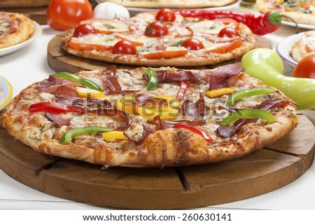 Pizza on wooden board served on the table. - stock photo
