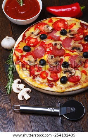 Pizza on wooden table with ingredients and cutter