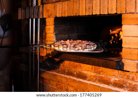 Pizza out of bread oven - stock photo