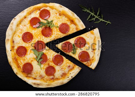 Pizza peperoni on stone black try with rocket and mozzarella cheese