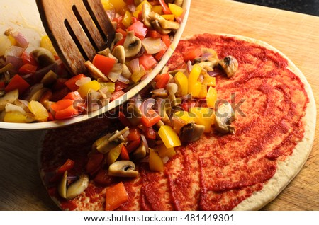 Pizza preparation scene.  Mixed, fried vegetables being tipped on to pizza from pan with wooden spatula.