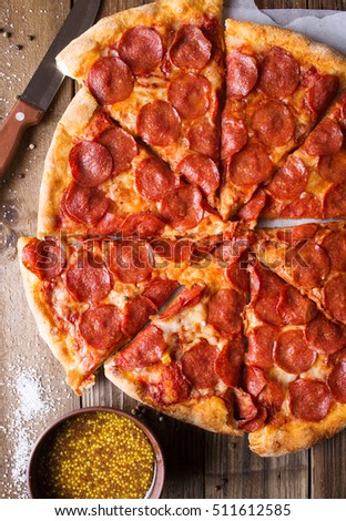 Pizza salami on wooden background