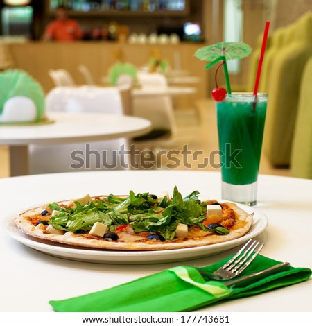 Pizza served with drink on white tabletop in pizzeria closeup composition - stock photo