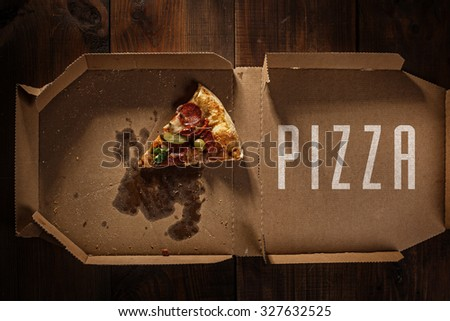 pizza slice in the in delivery box with pizza text on the wood - stock photo