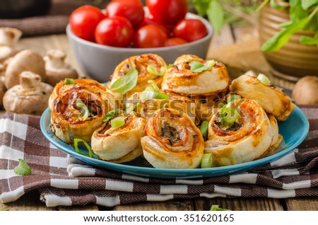Pizza snails in puff pastry with ham, cheese and mushrooms